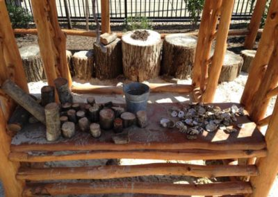 Shells, sand, chunks of wood and buckets are an invitation to create
